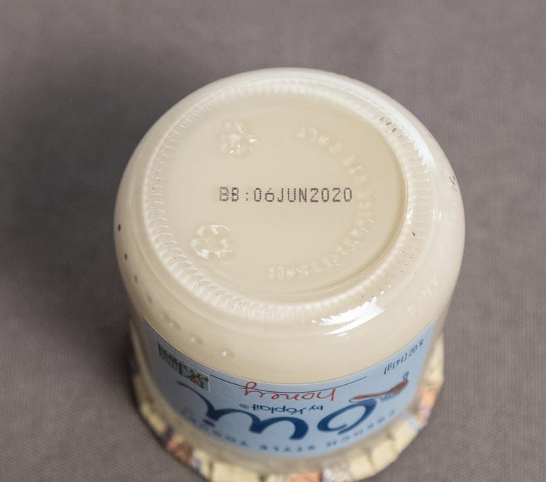 Glass yogurt jar with best by date imprint on bottom