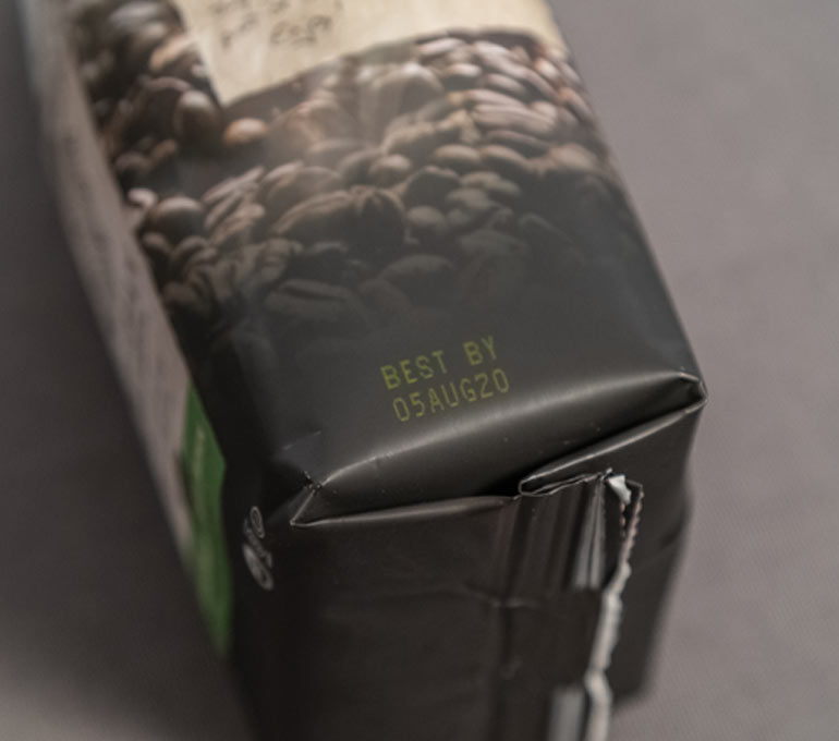 dark plastic coffee bag with yellow ink imprint of best by date